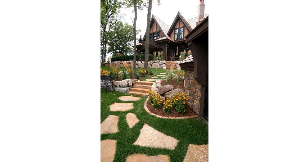 """""""2013 MWH Luxury Tour Home"""" View From Lake Minnetonka Looking up at the House. Limestone Path leading to Paver Patio with Custom Stone Fireplace."""