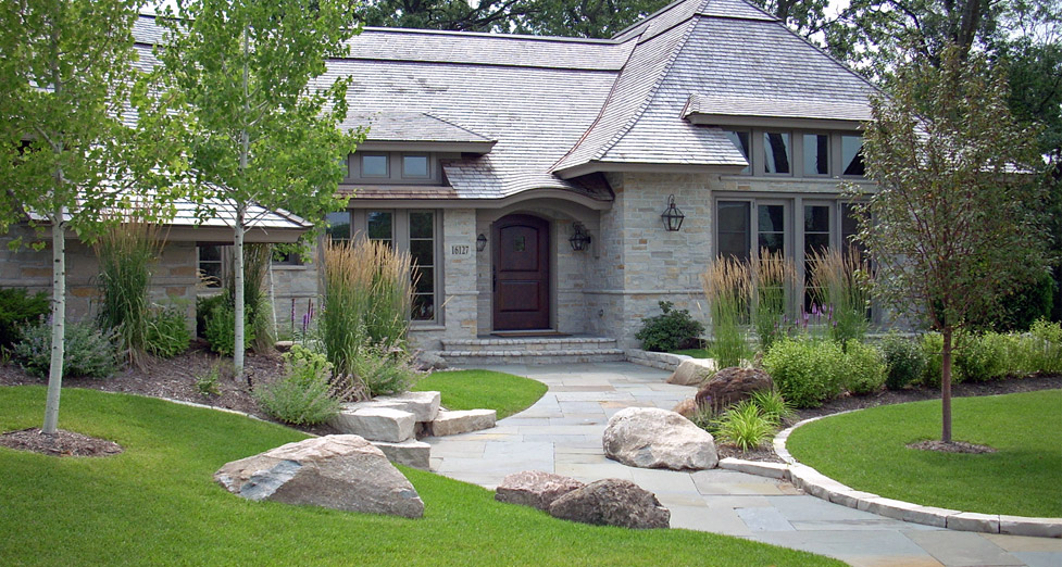 "We Installed a Bluestone Walkway, Limestone Seating Area, Boulder Accents, and Layered Plantings for a ""Natural Look""."
