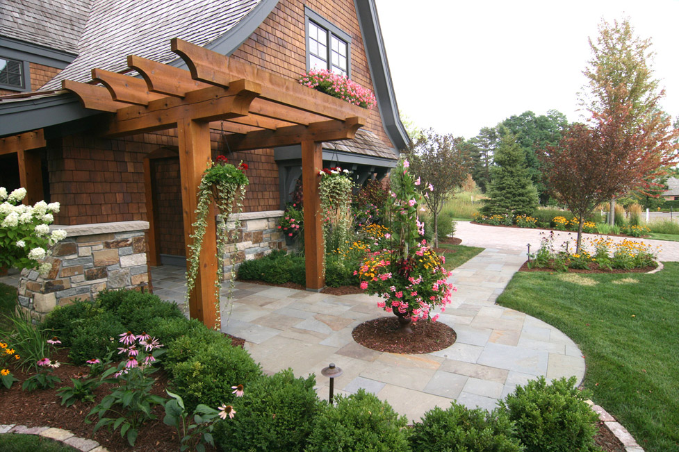 This Circular Front Entry was Designed with Buestone Walkway, Cedar Pergola, Stone Edging, and Plantings