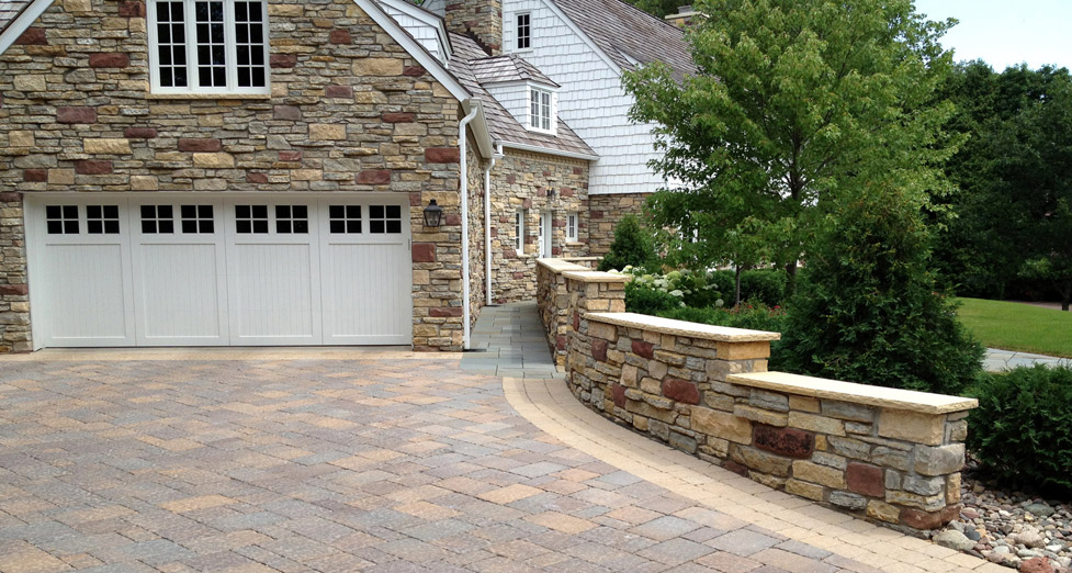 This Driveway and Front Entry Remodel was Customized with a Paver Driveway, Limestone Mortared Wall, Bluestone Walkway, and Plantings.