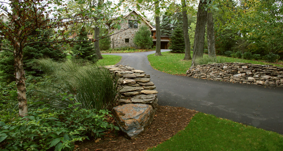 "This ""Hidden Gem"" Entry Way is Adorned by Two Dry-Laid Stone Walls and Natural Plantings."