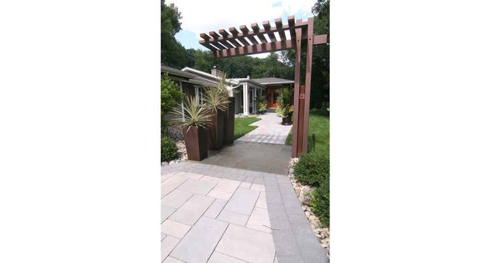 "An Updated Front Entry to this ""Suburban Rambler"" with a Paver Walkway, Bluestone Pad under a Custom Metal Arbor and Plantings"