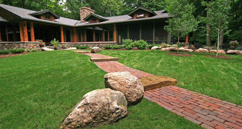 "This Home Was Designed to Feel Like a ""Upnorth"" Cabin. We Used Boulder Accents and a Paver Walkway with Limestone Steps"