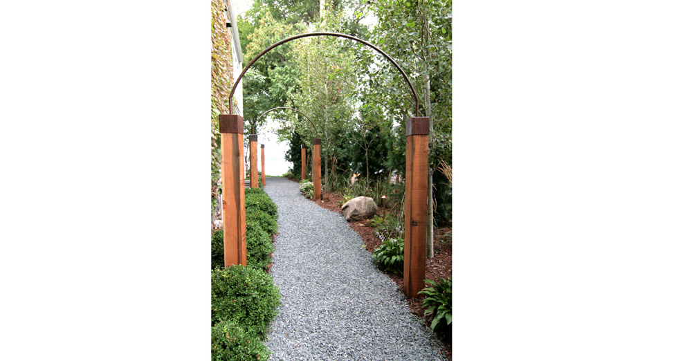 Custom Metal Arches Attached to Solid Wood Posts to Create a Walkway to the Lake.
