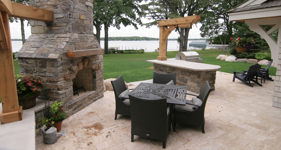 Lake Home Customized with a Flagstone Fireplace, Outdoor Kitchen, and Travertine Patio
