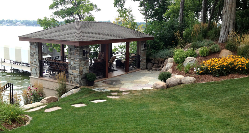 Lake House with a Flagstone Patio and Walkway, with Boulder Retaining Walls, Plantings, and Limestone Steps Down to the Lake.