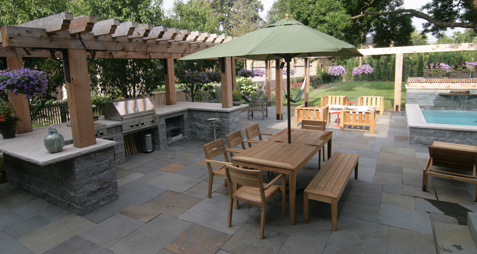 Outdoor Entertaining in the City, Equipped with Kitchen, Concrete Spa, Bluestone Patio, Flagstone Firepit, and Lounging in Hammocks.