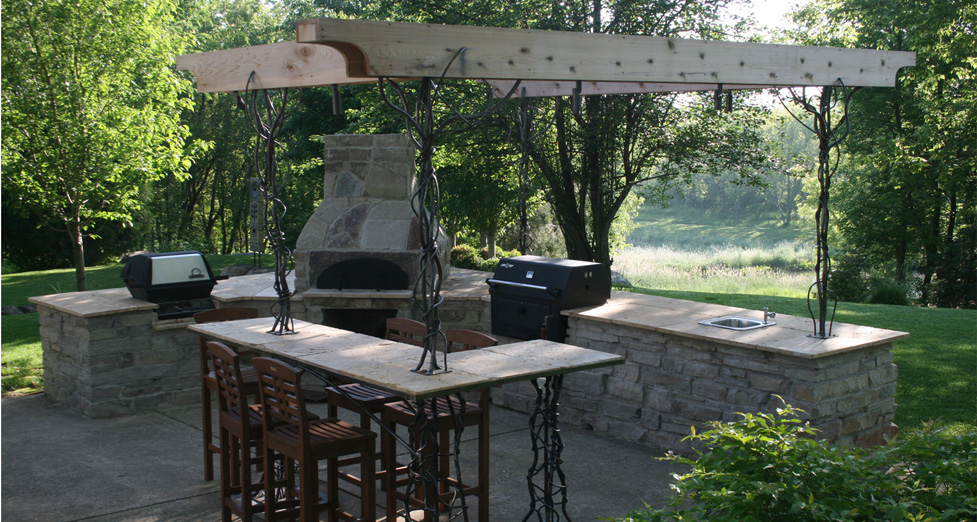 """Cooks Dream"" Outdoor Kitchen with Flagstone Base, Travertine Countertops, Metal/Wood Arbor, Pizza Oven, & Grills."