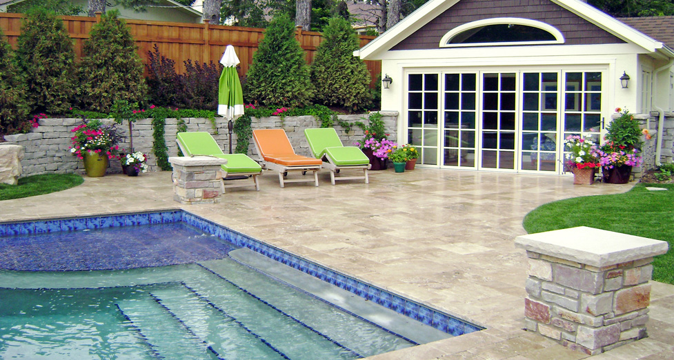 Custom Concrete Pool with a Submerged Tiled Sundeck, Limestone Pillars, Travertine Pool Deck and Pool House for Entertaining.