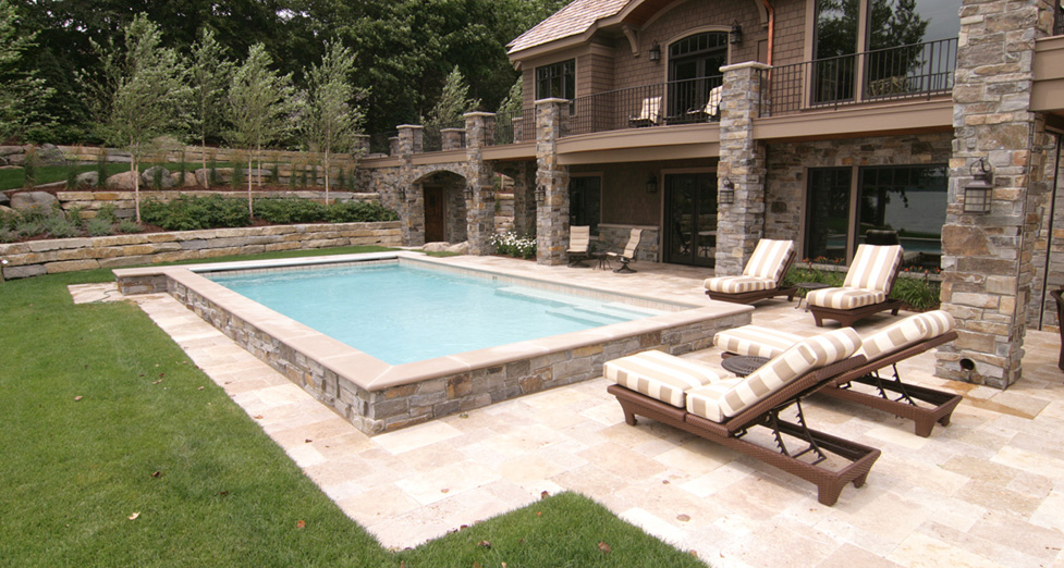 Raised Concrete Pool With Limestone Detail And Travertine Patio. Limestone  Tiered Walls With Plantings.