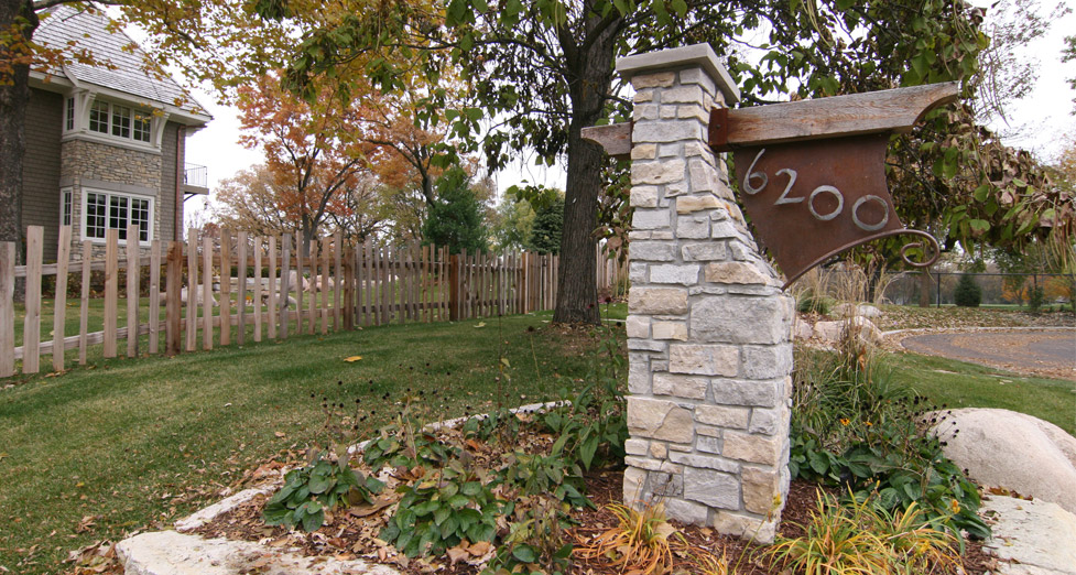 Stone Address Pillar with Metal Address Numbers and Strip Rail Fence