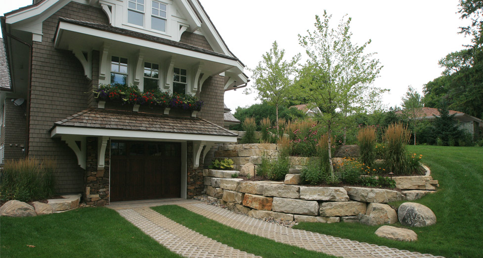 Concrete and Grass Pavers with Limestone Retaining Wall