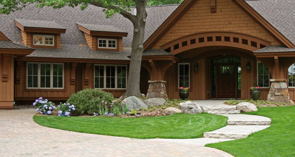 "The ""Curvature"" of this Architecture Inspired the Curved Paver Walkway and Drive with Limestone Slab Steps and Greenery."