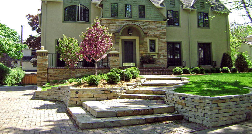 "An ""Edina Remodel"" Achieved Using Cobblestone Pavers, Limestone for the Walls and Steps, Along with Varied Plantings."
