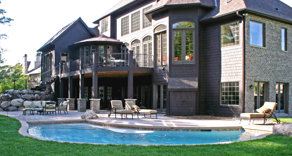 """This Custom Concrete Pool Accents the """"Curves"""" of the House & Blends into the Paver Patio."""