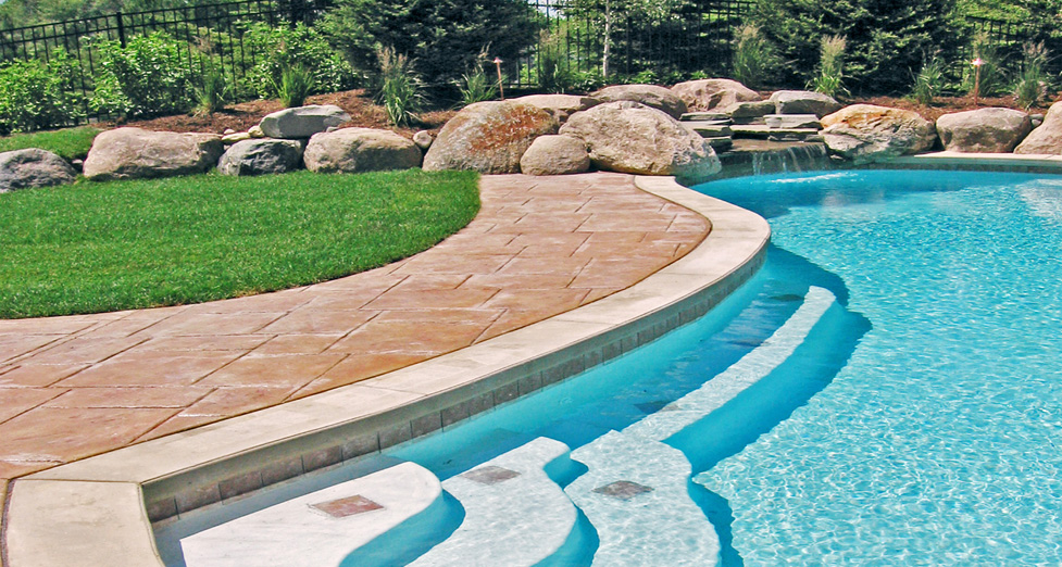 Curved Stamped Concrete Pool Deck Accented with Curved Pool Steps and Boulder Water Fall.