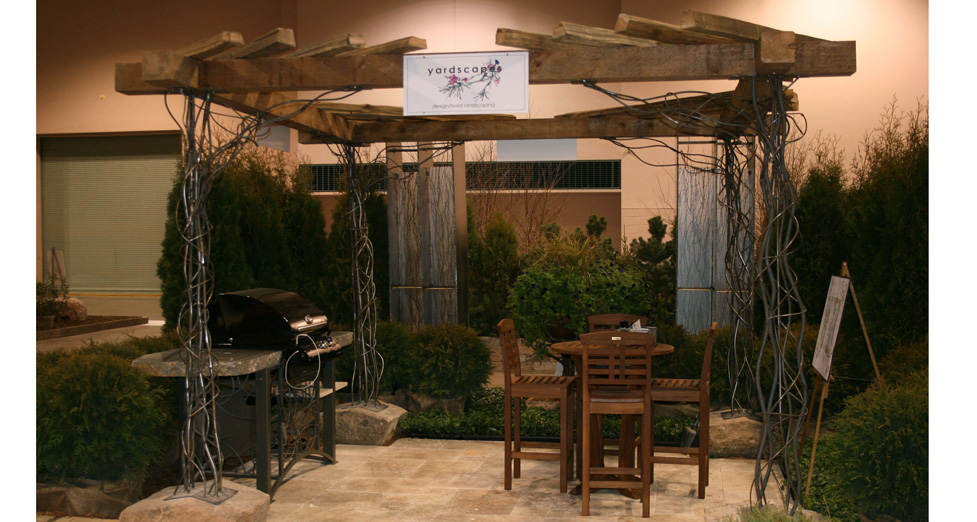 Custom Metal Grill Stand with Cut Boulder Shelves Under Wooden Arbor with Custom Metal Legs.