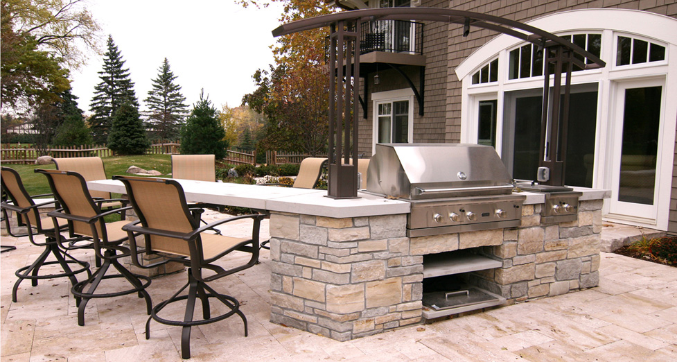 "Custom Outdoor Kitchen with the ""Open-Concept"" Feel Constructed out of Mortared Limestone and Indiana Limestone Countertop. The Patio is Dry-Laid Travertine Stone."