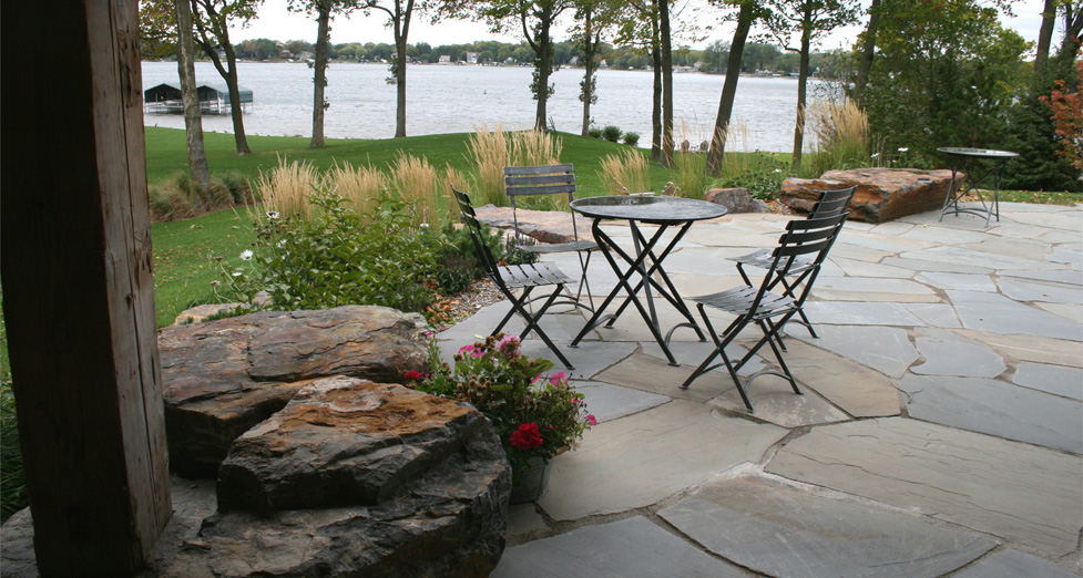 "This ""Lake Escape"" has an Irregular Bluestone Patio with Masabi Stone Outcroppings & Plantings."