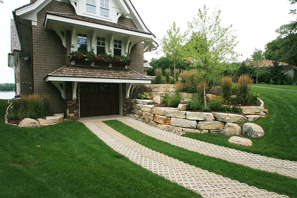 Permeable paver driveway with limestone retaining walls and bould outcroppings