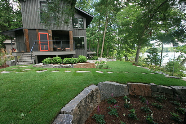 Wisconsin cabin with granite natural stone slabs for slight retaining for a flatter yard