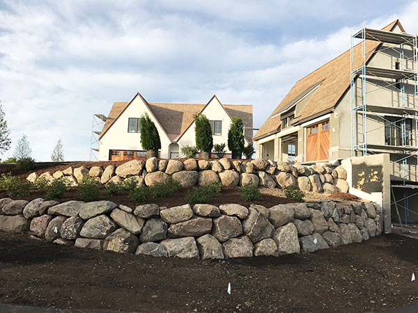 large boulder walls with boxwood plantings