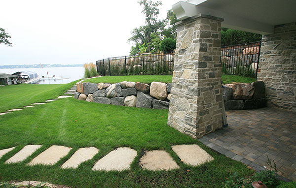Lake Minnetonka Minnesota underdeck paver patio, limestone steppers, boulder retaining wall with metal fence enclosure