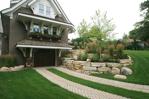 Limestone Retaining wall with Boulder outcroppings, Pavers Concrete grass Pavers, Plantings single Stem Birch, Native Grasses, Perennials. Shorewood, mn