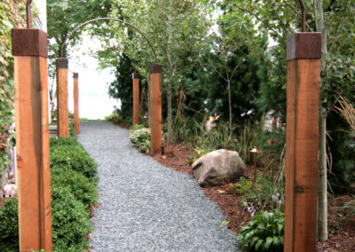 Custom Metal and Wood Arches Over Pathway to Lake