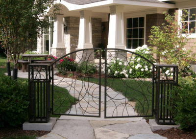 Front Entry with Custom Metal Gate, Limestone Pathway, and Cobblestone Paver Driveway