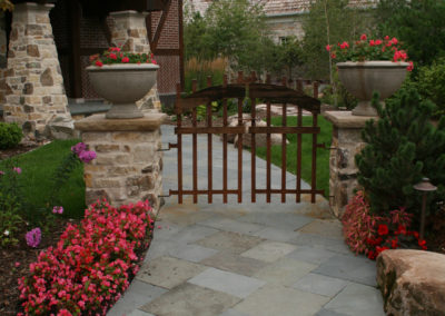 Irregular Bluestone Walkway with Mortared Limestone Pillars and Custom Wood Gate