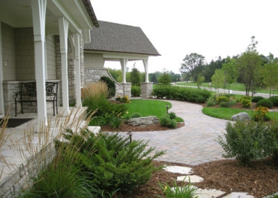 Paver Walkway to Front Entrance with Boulder Outcroppings and Varied Plantings