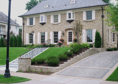 Traditional Home Front Entry with Limestone Retaining Wall and Paver Driveway