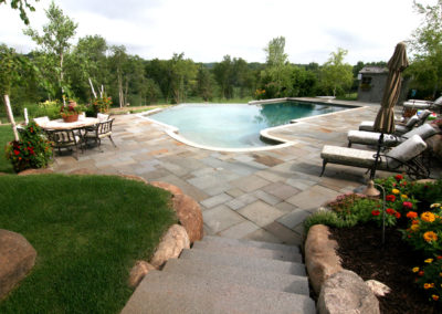 Custom Concrete Vanishing Edge Swimming Pool with Bluestone Patio