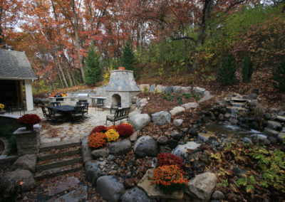 Outdoor Kitchen and Fireplace Built into the Boulder Wall