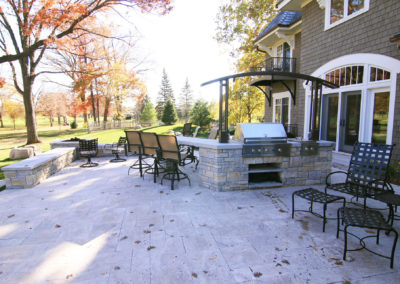 Custom Outdoor Kitchen and Bar Area with Metal Arbor and Downlights