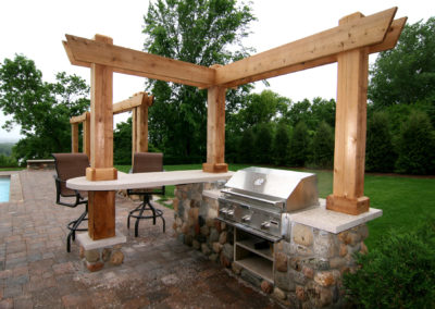 Poolside Outdoor Kitchen in Eden Prairie, MN with Mortared River Rock and a Cedar Pergola