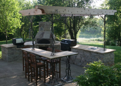 Limestone and Travertine Outdoor Kitchen with a Custom Metal and Cedar Pergola