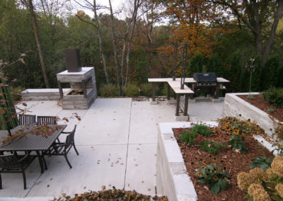 Modern Outdoor Kitchen with Custom Metal and Limestone with Concrete Fireplace