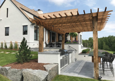 Modern Country Entertaining with Concrete Outdoor Kitchen, Cedar Pergola, and Granite Block Retaining Walls