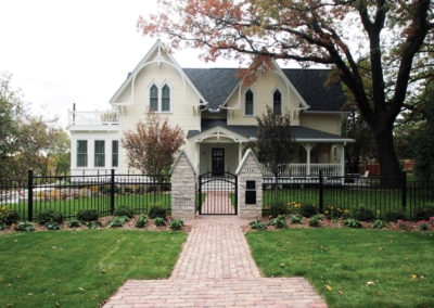 Historic Stillwater, MN Home Remodeled with Custom Metal Fencing and Gate, Cobblestone Pavers, and Mortared Limestone Pillars