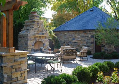 Limestone Upright Fireplace and Outdoor Kitchen on a Paver Patio